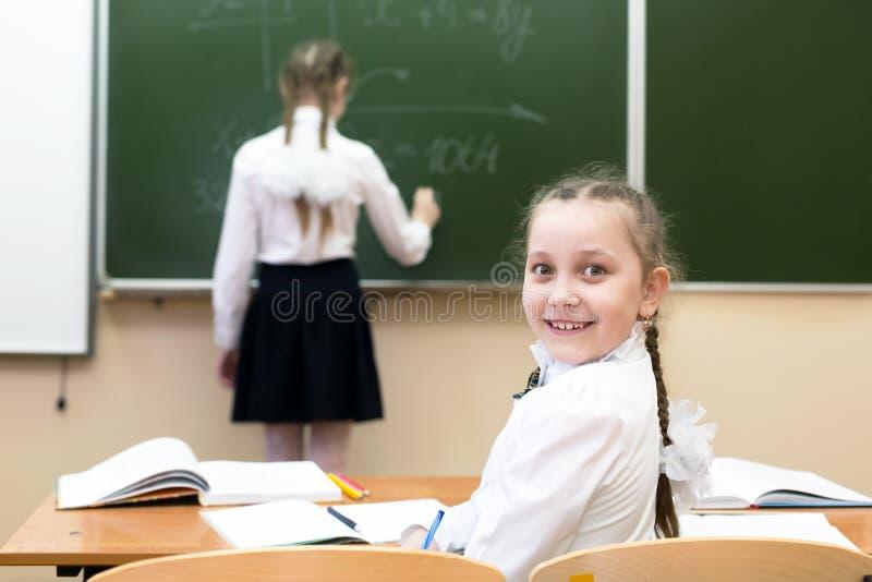 Schulmädchen schaut zurück, während ein Freund an der Tafel schreibt lizenzfreies stockbild