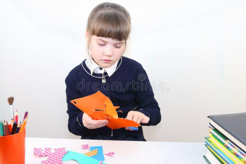 Schulmädchen schnitt mit Scheren von farbigem Papier heraus stockbild