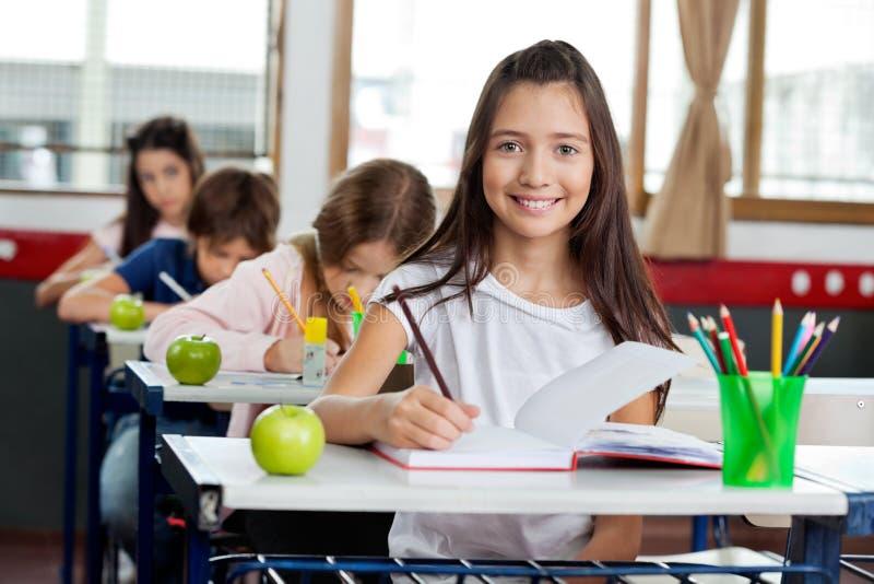 Schulmädchen-Schreiben im Buch am Klassenzimmer lizenzfreie stockbilder
