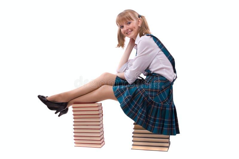 Schulmädchen sitzt auf dem Stapel des Buches. lizenzfreies stockbild