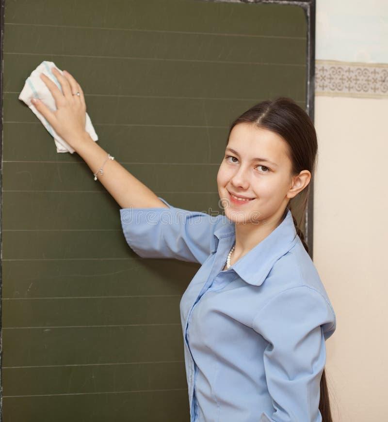 Schulmädchen wäscht Tafel stockfotografie