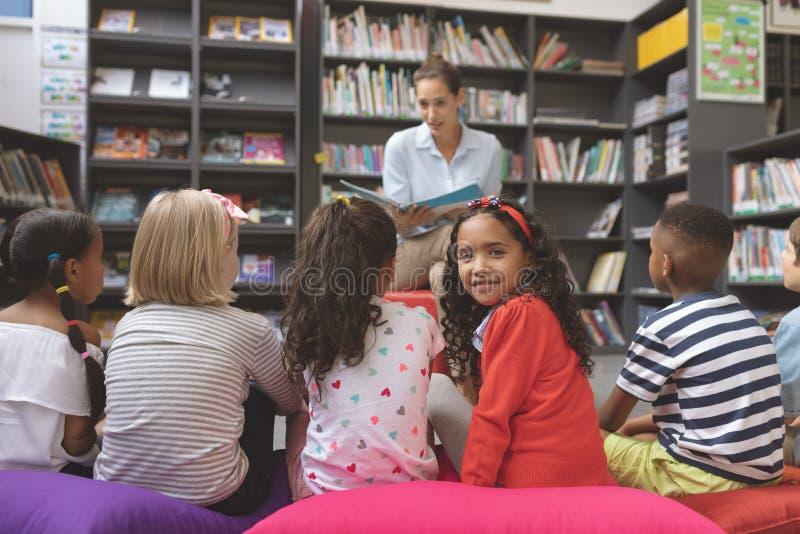 Schulmädchen, welches die Kamera betrachtet, während andere hörenden Kinder die Geschichtenerzählen durch ihren Lehrer schulen stockfotos