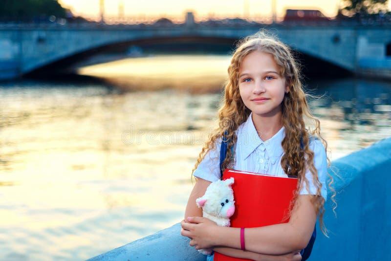 Schulmädchenblondine mit blauen Augen steht nahe dem Fluss in der Stadt bei Sonnenuntergang lizenzfreie stockbilder