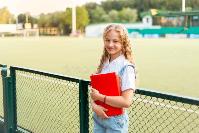 Schulmädchenblondine mit den blauen Augen, die einen roten Ordner und einen Rucksack halten lizenzfreie stockfotos