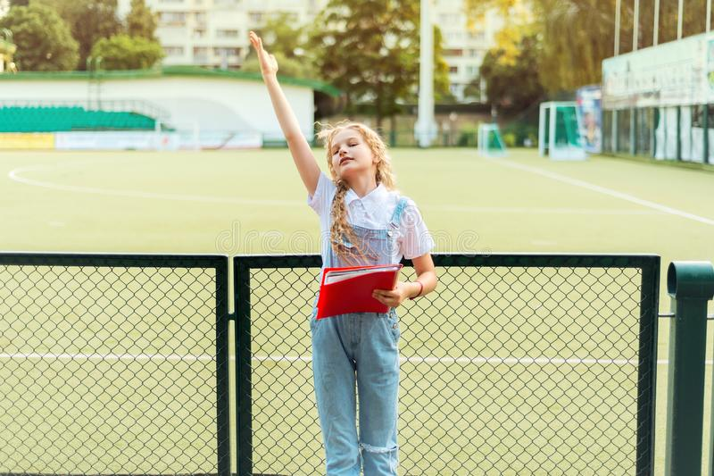 Schulmädchenblondine und -erhöhungen ihre Hand oben lizenzfreies stockbild