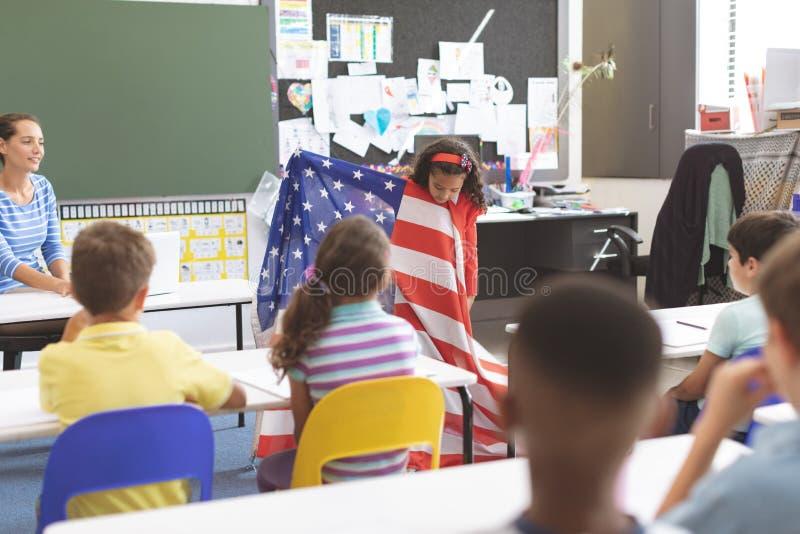Schulmädchenholdingamerikanische flagge im Klassenzimmer stockfotografie