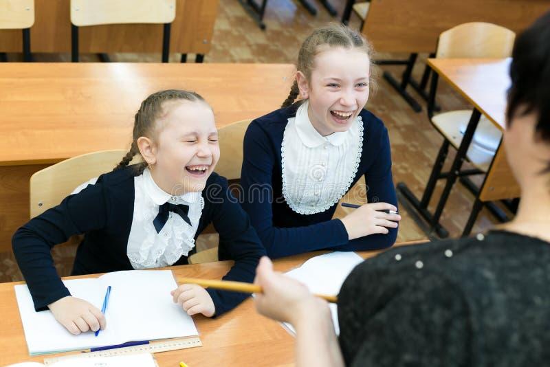 Schulmädchenjugendliche lachen über ihren Lehrer stockbild