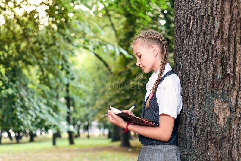 Schulmädchenjugendlicher, der ein Buch in einem Park nahe einem Baum liest lizenzfreie stockfotografie