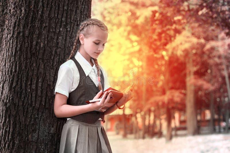 Schulmädchenjugendlicher, der ein Buch in einem Park nahe einem Baum liest lizenzfreies stockfoto