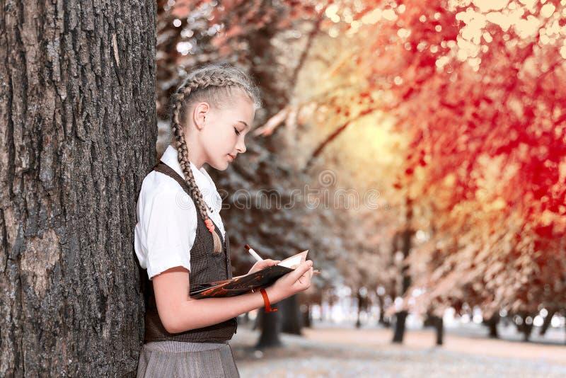 Schulmädchenjugendlicher, der ein Buch in einem Park nahe einem Baum liest lizenzfreie stockbilder