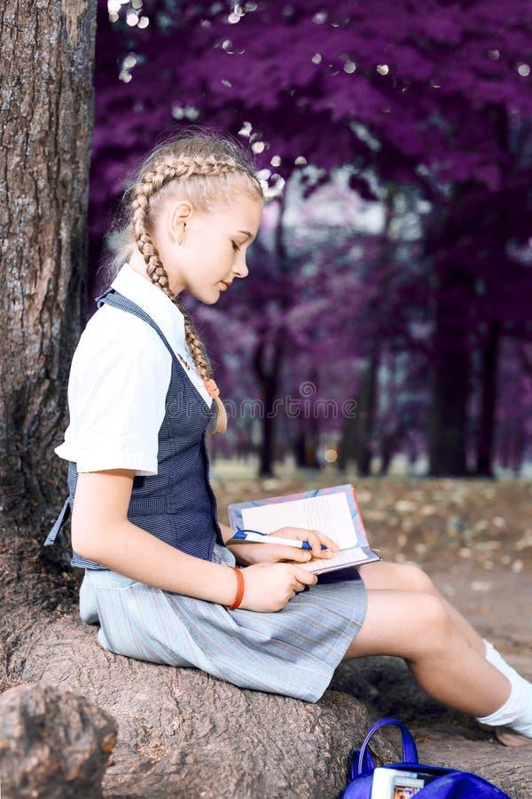 Schulmädchenjugendlicher, der ein Buch in einem Park nahe einem Baum liest stockbilder