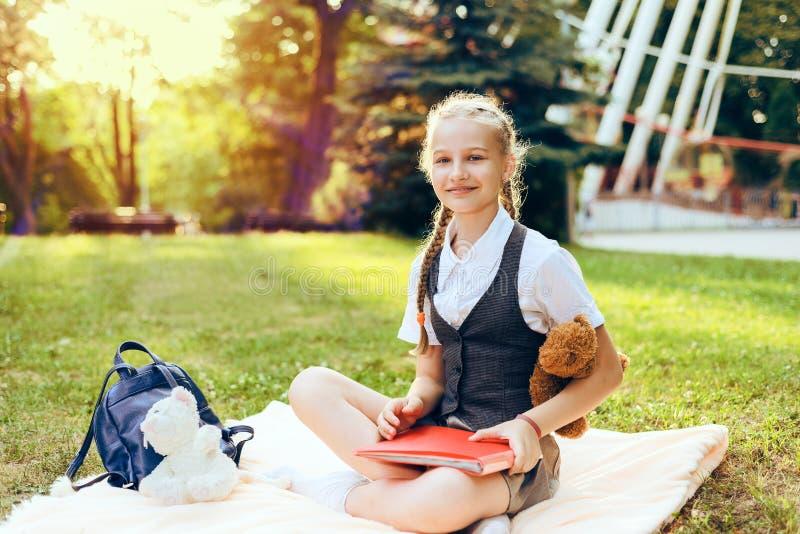 Schulmädchenjugendlicher mit Zöpfen mit Büchern und Notizbuch lizenzfreie stockfotografie