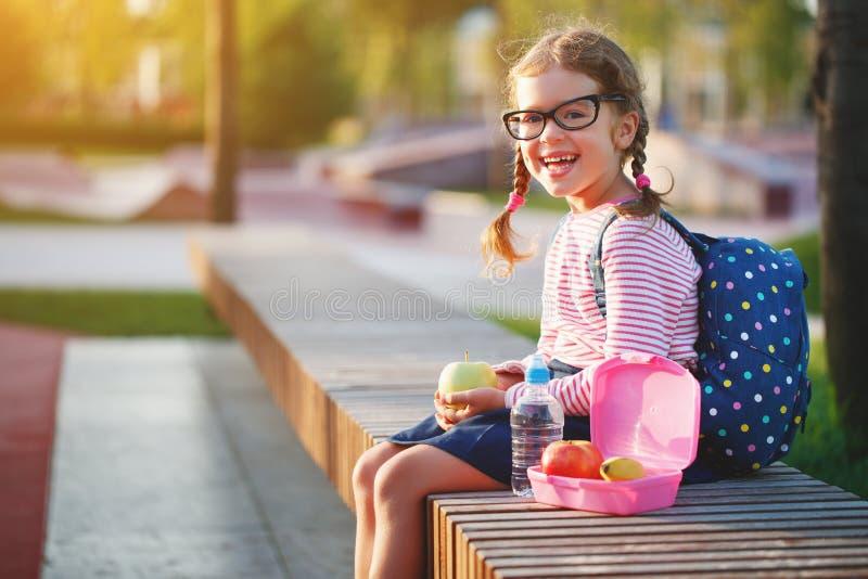 Schulmädchenkind, das in der Schule Mittagessenäpfel isst lizenzfreie stockfotos