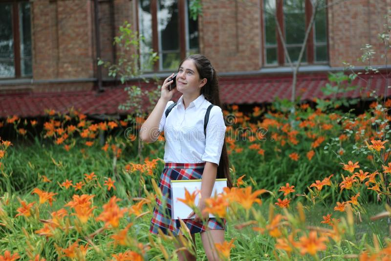 Schulmädchenmädchen mit dem langen Haar in der Schuluniform sprechend am Telefon stockfoto