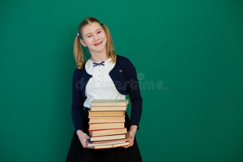 Schulmädchenmädchen während einer Lektion an der Tafel mit Büchern lizenzfreie stockfotos