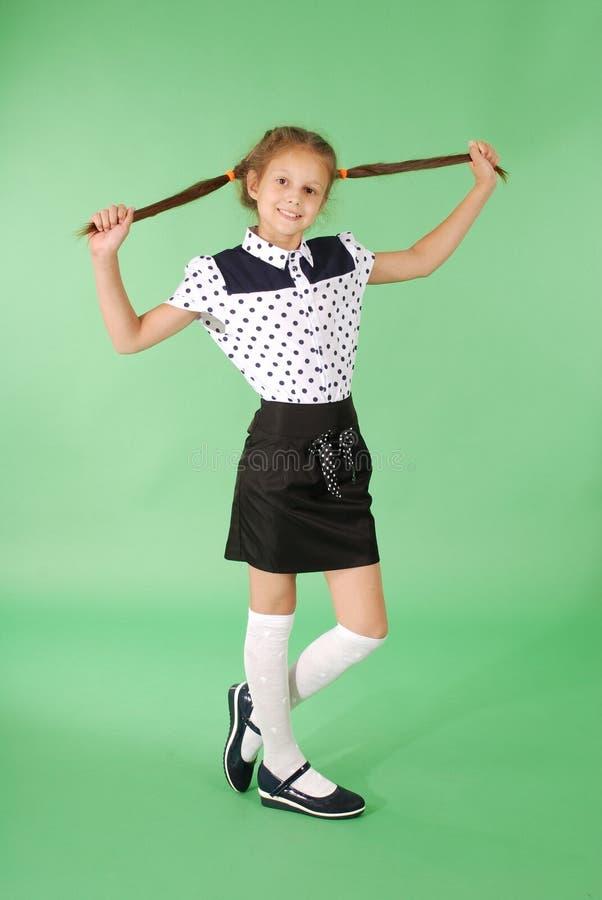 Schulmädchenspiele mit dem geflochtenen Haar stockbild