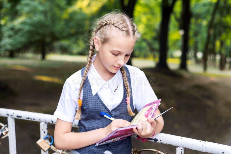 Schulmädchenstift, der eine Aufgabe in einem Notizbuchstudieren schreibt lizenzfreie stockfotos