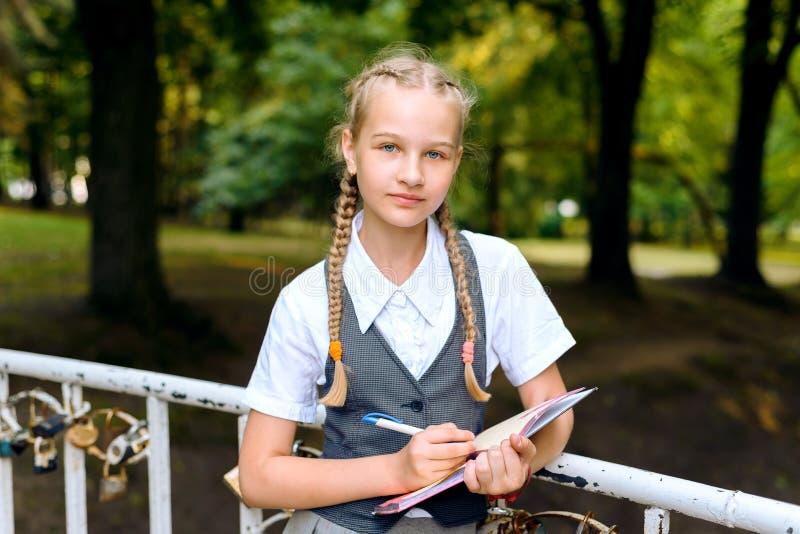 Schulmädchenstift, der eine Aufgabe in einem Notizbuchstudieren schreibt lizenzfreies stockfoto