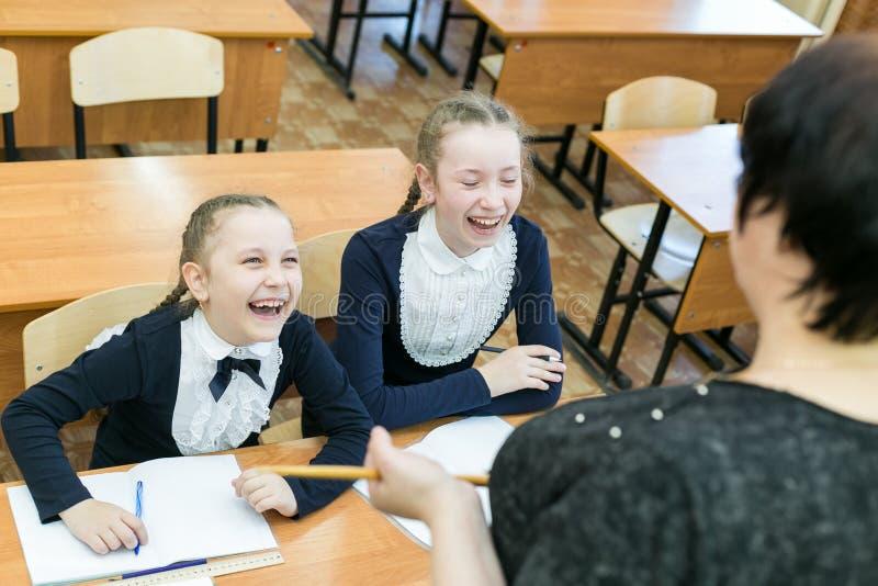 Schulm?dchenjugendliche lachen ?ber ihren Lehrer lizenzfreie stockfotografie
