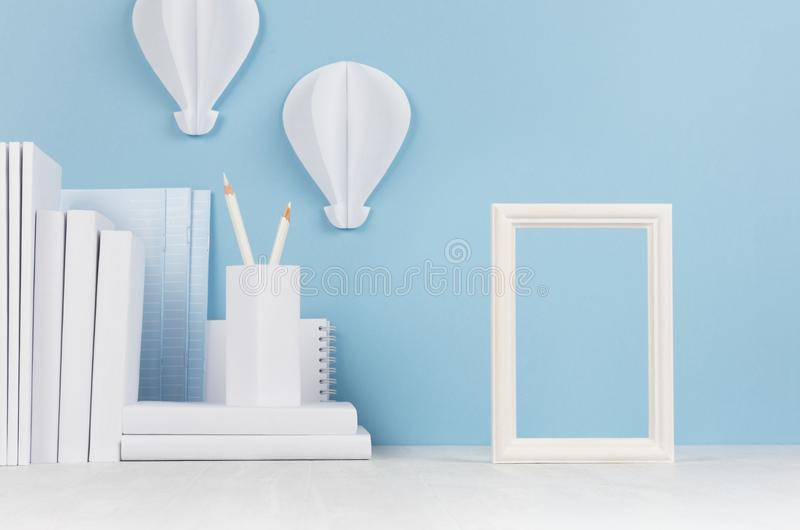 Schulschablone - Weißbüche, Briefpapier, leerer Fotorahmen und dekorativer Ballonsorigami auf weißem Schreibtisch und weich Blau stockbild