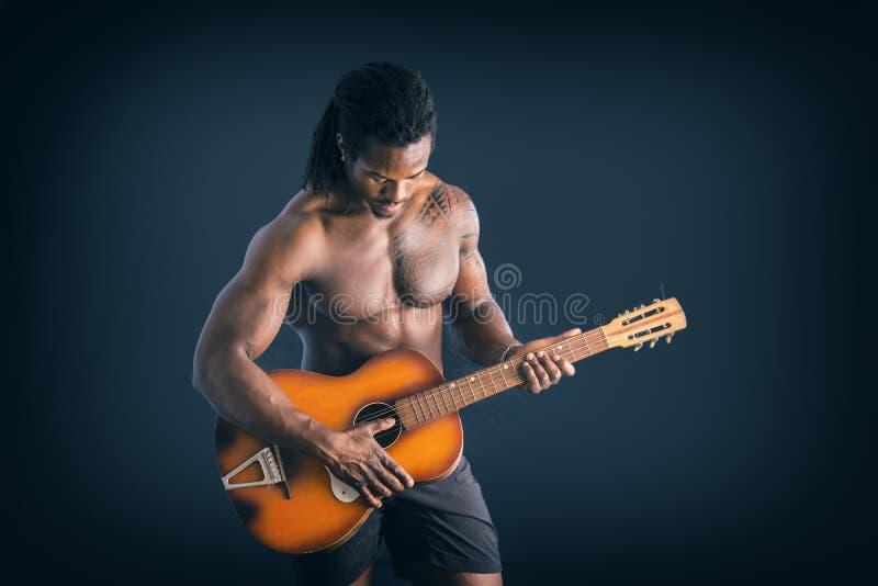 Schulterfreier junger schwarzer Mann Nuscular, der Gitarre spielt stockfotos