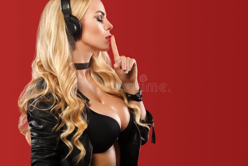 Schulterfreies DJ und PJ, hörende Musik der recht blonden Frau mit ihren Kopfhörern auf dem roten Hintergrund stockfotografie