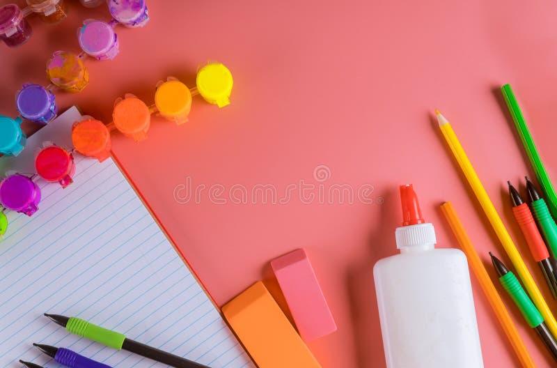 Schulzusätze auf einem rosa Hintergrund Farbe, Bleistifte, Kleber stockfotografie