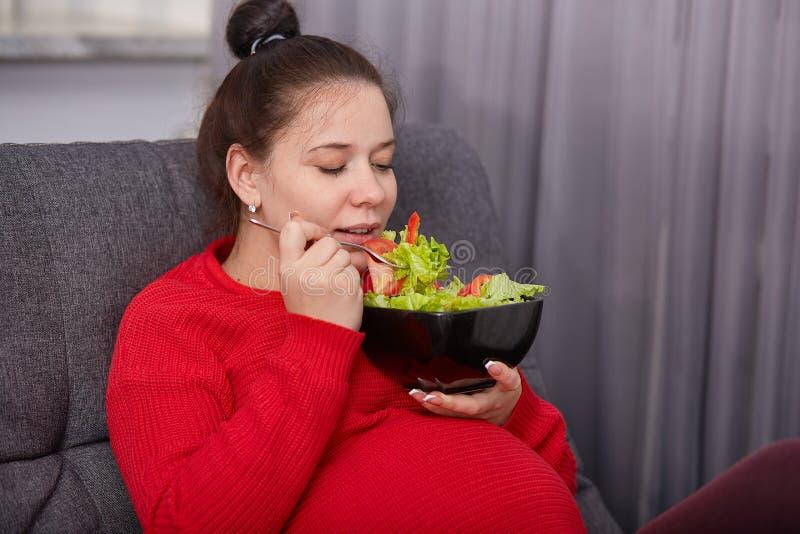 Schuss der attraktiven brunette schwangeren netten Frau genießt, frischen Salat von Tomaten und von Kopfsalat, Haltungen an zu es stockfotografie