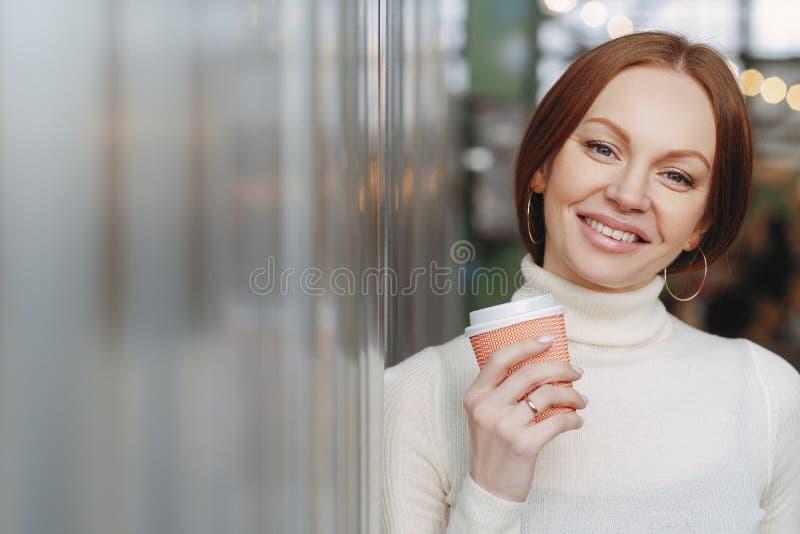 Schuss der attraktiven Frau mit toothy Lächeln, hat das Make-up, gekleidet in der weißen Rollkragenstrickjacke mit Kragen, hält K stockbilder