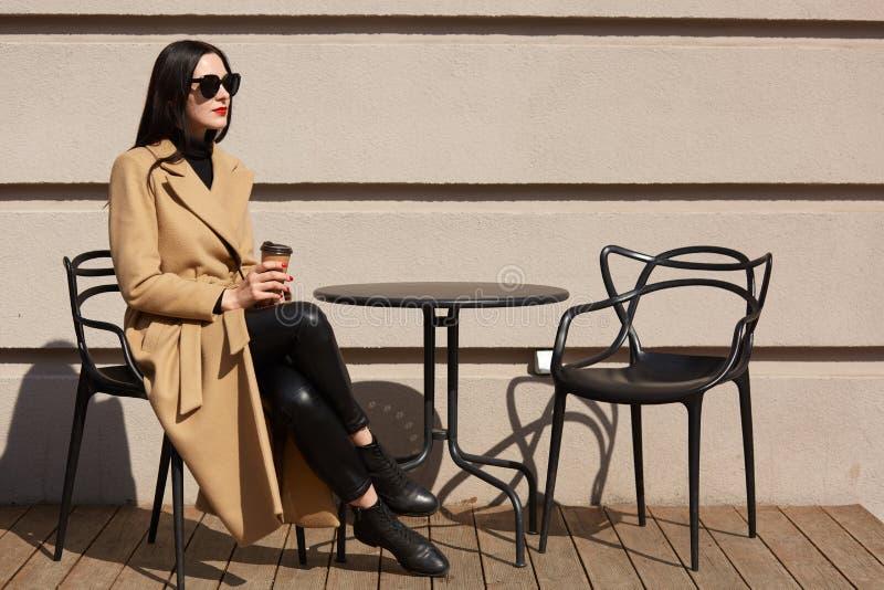Schuss der Frau den modernen Mantel tragend, der Café der gemütlichen Straße im im Freien frühstückt und Kaffee vom Papierbecher  lizenzfreie stockbilder