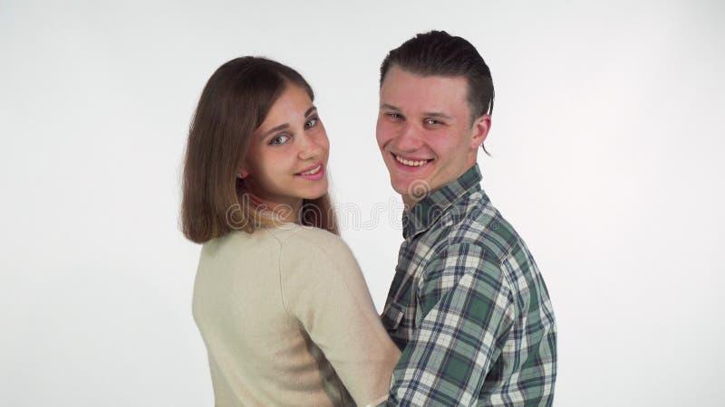 Schuss der hinteren Ansicht eines Paares, das, wendend an die Kamera über ihren Schultern umarmt stockfoto
