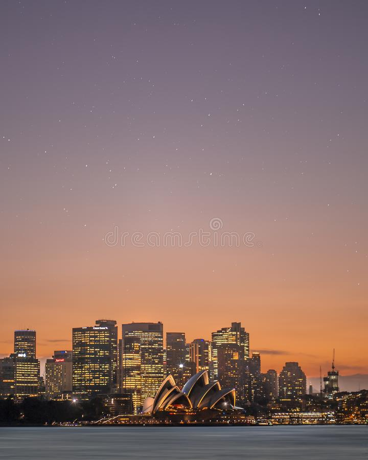 Schuss der langen Strecke von Sydney-Skylinen mit Wolkenkratzern während des Sonnenuntergangs lizenzfreies stockbild