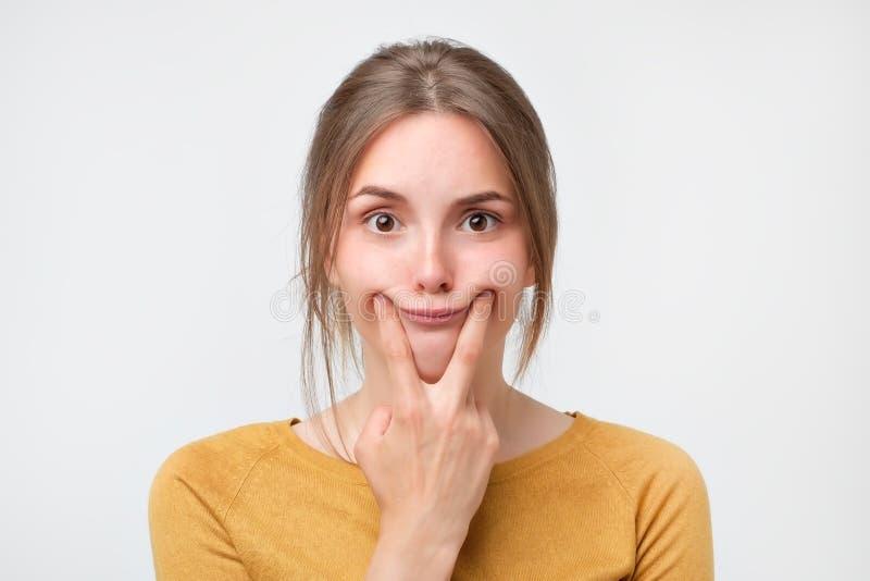 Schuss der schönen kaukasischen Jugendlichen, die ein Lächeln, ihre Finger an den Rändern ihrer Lippen halten zwingt lizenzfreie stockfotos