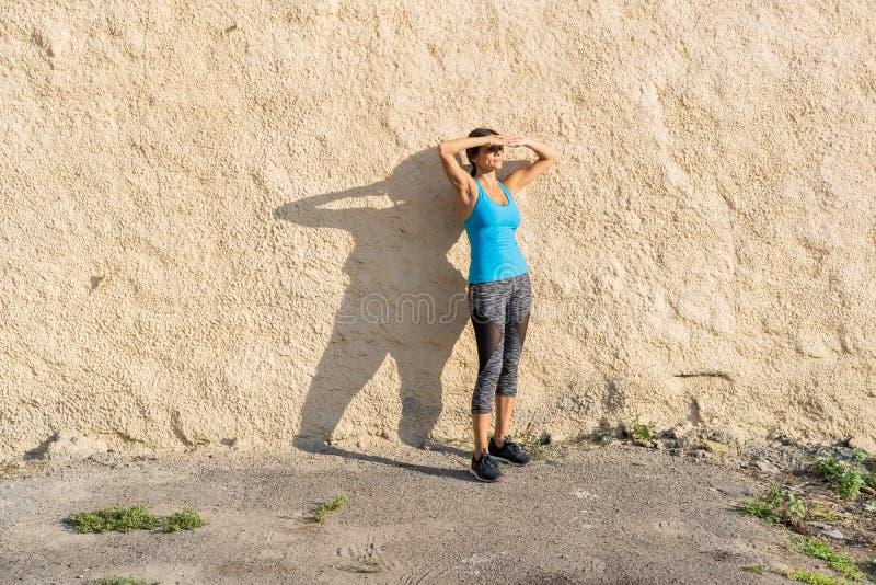 Schuss des Sitzläufers draußen stehend gegen eine Wand Sportliche Frau, die nach laufender Übung sich entspannt stockfotos