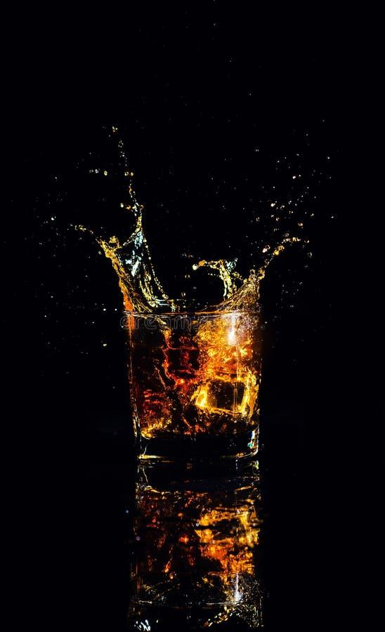 Schuss des Whiskys mit Spritzen auf schwarzem Hintergrund, Weinbrand in einem Glas lizenzfreie stockbilder