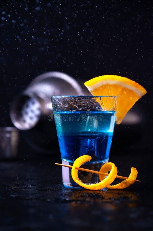 Schuss mit weißem Rum, Alkohol blaues Curaçao und orange Scheibe Alkoholisches Schicht-Cocktail mit Schüttel-Apparat auf dunklem  lizenzfreie stockfotos