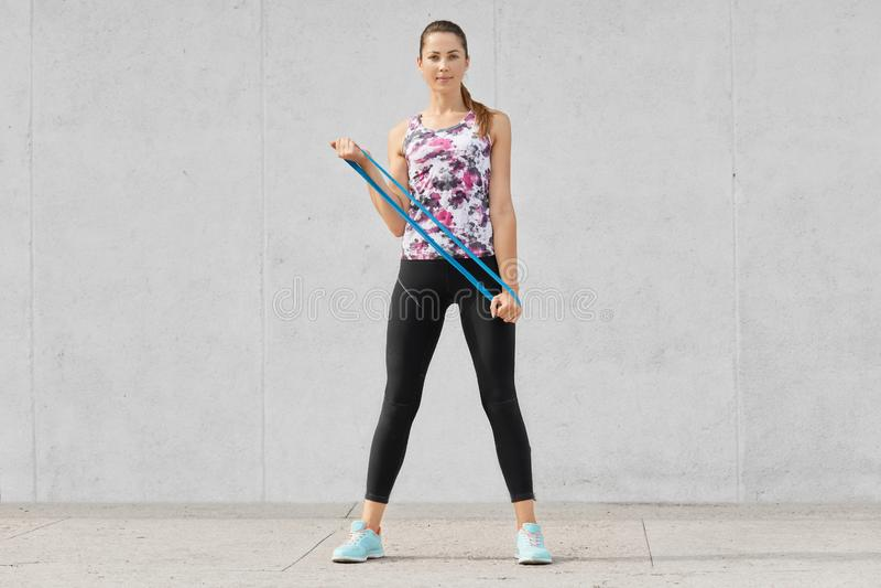 Schuss in voller Länge der attraktiven dünnen Frau in der Sportkleidung tut Armübungen mit Eignungsgummi, verwendet die elastisch lizenzfreies stockfoto