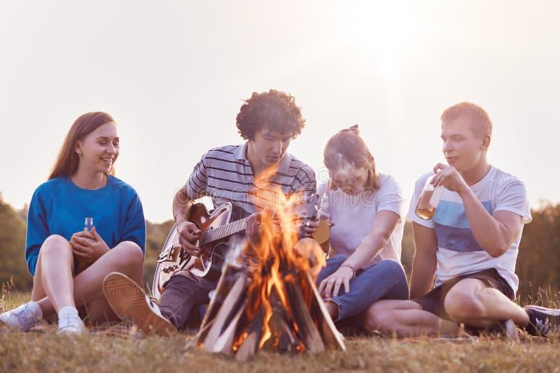 Schuss von gut weiblichen und männlichen Freunden genießen Sommertag auf Picknick, spielen Akustikgitarre, sitzen nahe Lagerfeuer lizenzfreie stockfotos