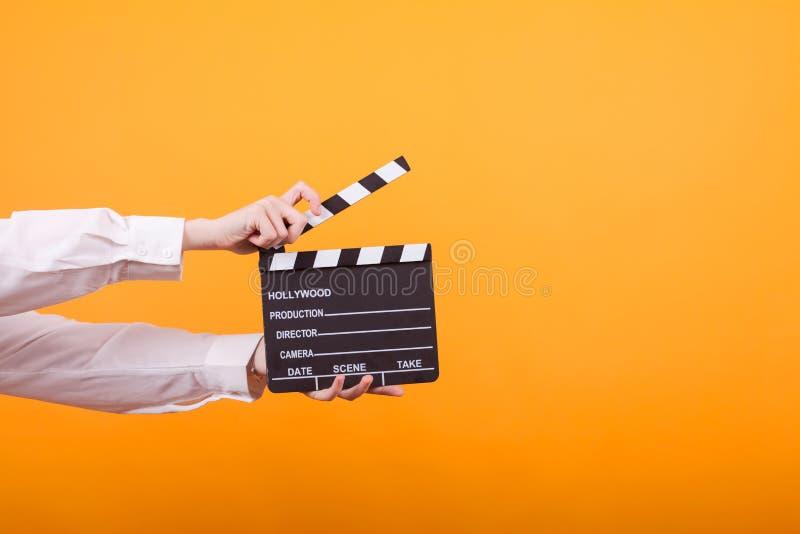 Schuss von lokalisierten Händen auf dem gelben Hintergrund, der ein Scharnierventil hält lizenzfreie stockbilder