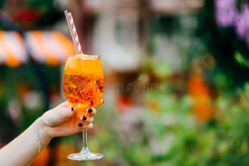 Schuss weiblicher ` s Hand mit neuem Sommergetränk des Maniküregriffs im Weinglas Orange kaltes Cocktail mit Eis, damit Sie gegen stockfoto