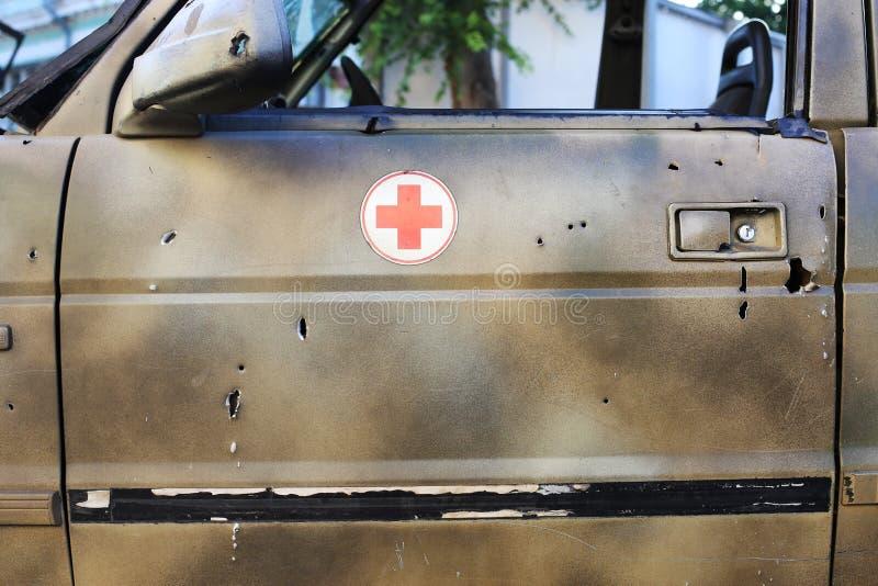 Schusskrankenwagen an der Szene von Feindseligkeiten Einschussl?cher im Metall lizenzfreies stockbild