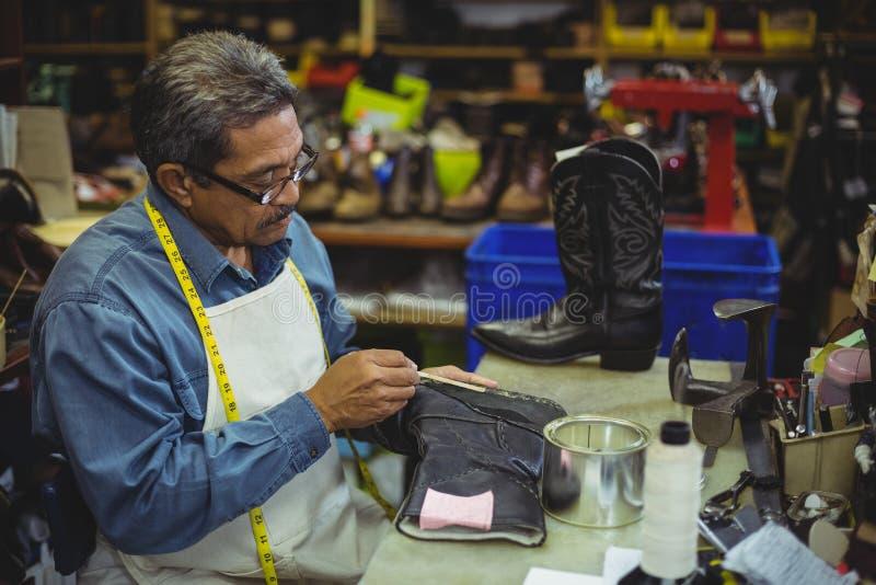 Schuster, der Kleber auf Schuh aufträgt stockbilder