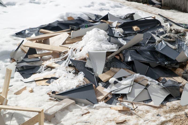 Schutt mit Dachschrott, der im Winter in der Nähe des im Bau befindlichen Hauses gelagert wird lizenzfreies stockfoto