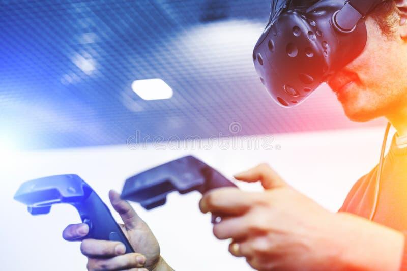 Schutzbrillen der Manngebrauchs-virtuellen Realität oder VR-Kopfhörer oder Sturzhelm, Spielvideospiel mit drahtlosen Prüfern, Zuk stockbilder