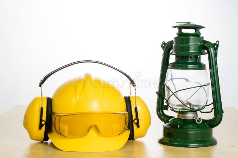 Schutzhelm- und Öllampe auf einem Holztisch Sicherheit und hea stockfotos