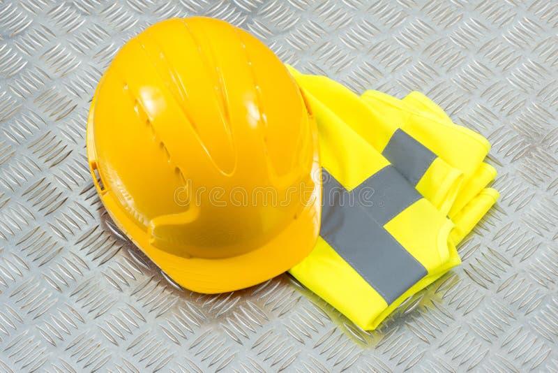 Schutzhelm und gefaltete Sicherheits-Weste auf Stahlwarzenblech lizenzfreies stockfoto