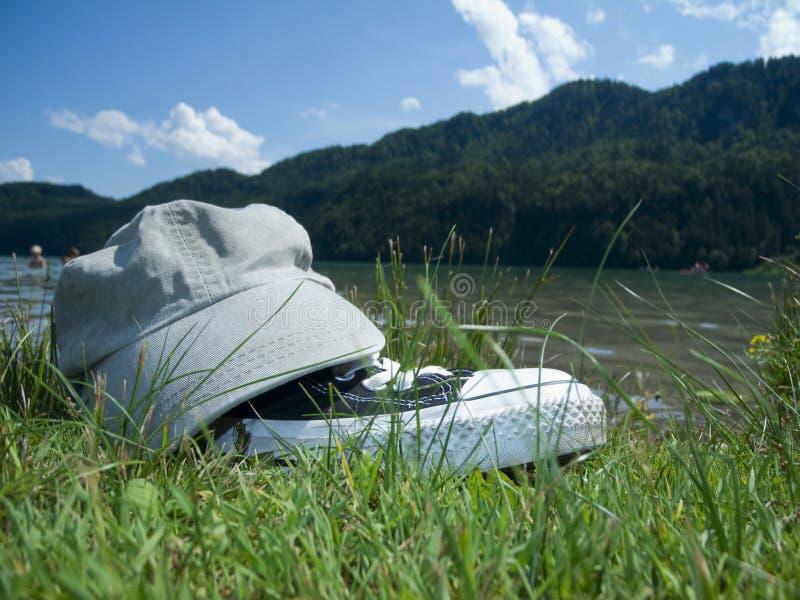 Schutzkappe und Schuhe durch den See stockbilder