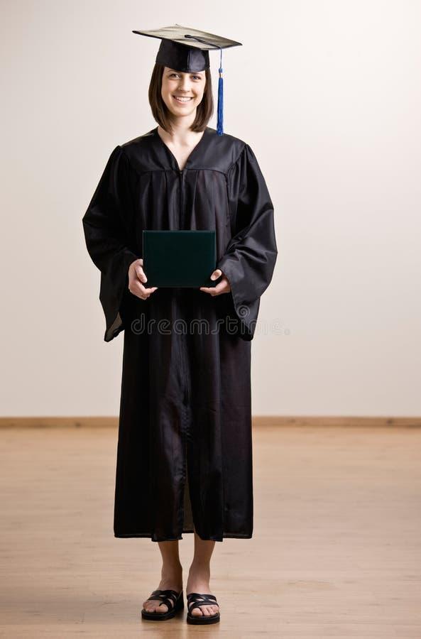 Schutzkappen- und Kleidholdingdiplom des Kursteilnehmers tragendes stockfotos