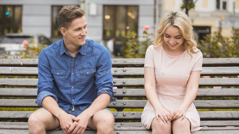 Schuw blondemeisje die, aantrekkelijke kerel die met mooie vrouw op bank flirten glimlachen royalty-vrije stock foto's