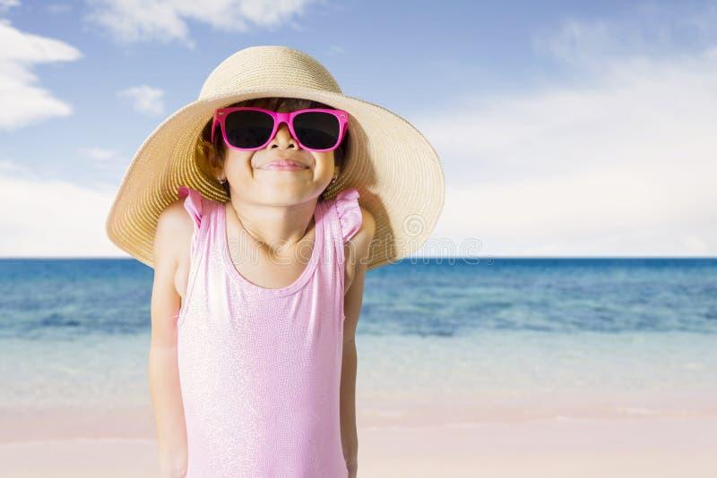 Schuw meisje die zonnebril op de kust dragen royalty-vrije stock fotografie